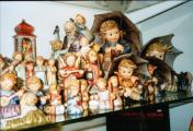 a lot of hummel figurines in the show case